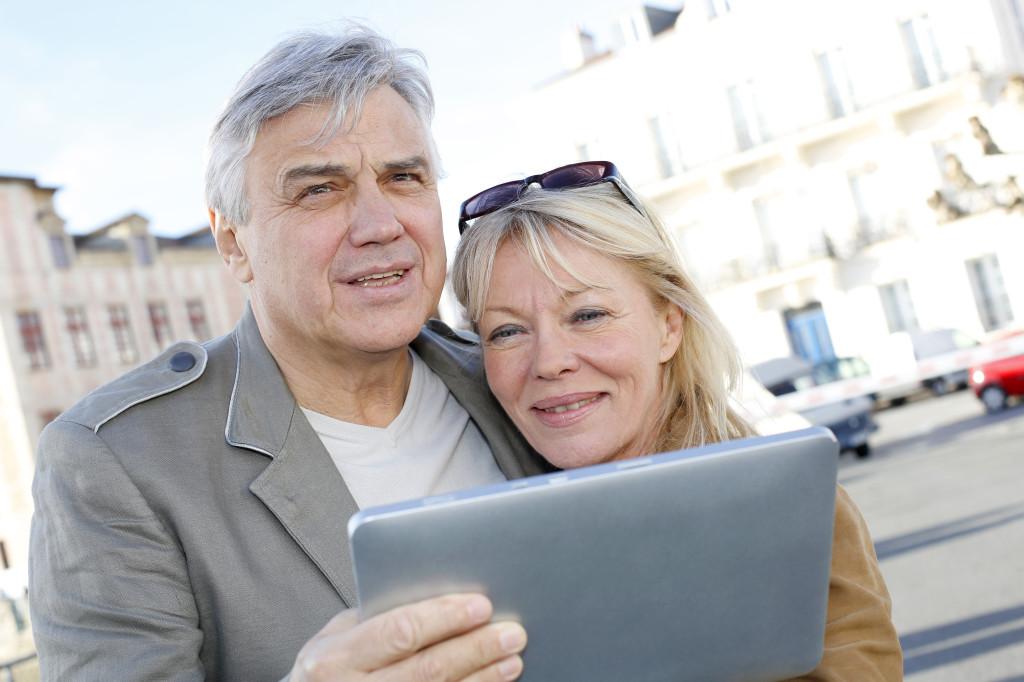 Couple on vacation using electronics
